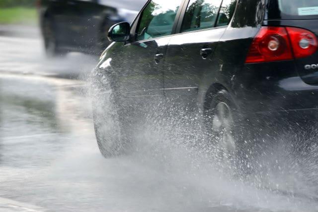 black car driving through rain