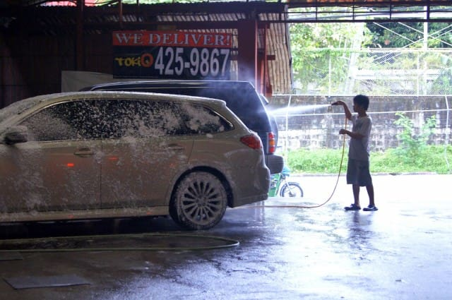 Boy washing a vehicle at a carwash