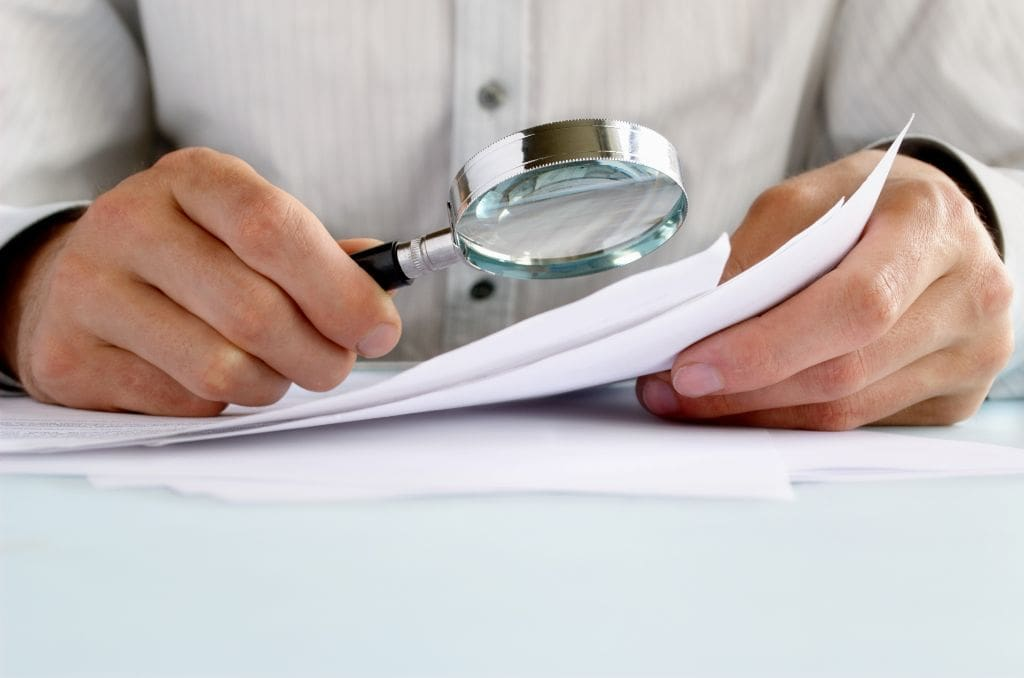 Man looking at documents through a magnifying glass